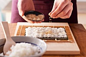 Maki sushi being prepared: rice being sprinkled with sesame seeds