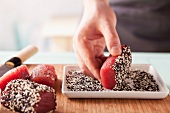 Tuna pieces being turned in black and white sesame seeds