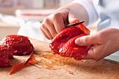 Die Haut von gerösteten Paprikaschoten abziehen