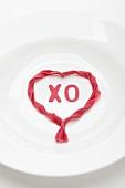 Weisser Teller mit Herzform aus roten Nudeln