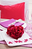 Festive place setting with rose petals arranged in heart