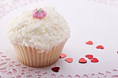 Cupcake with grated coconut and sugar flower