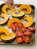 Squash slices and tomatoes being sprinkled with salt