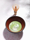 Matcha tea in a bowl, tea whisk