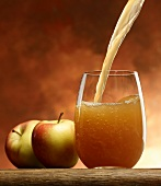 Pouring 'naturally cloudy' apple juice into a glass