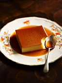 Creme caramel, with a bite out of it, on a plate with a spoon