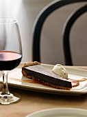 A slice of chocolate tart with caramel sauce and ice cream, and a glass of red wine
