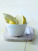 Lemon halves and lemon slices in a small bowl