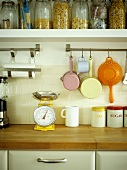 Vintage-style kitchen utensils hanging from stainless steel rail below shelf with storage jars