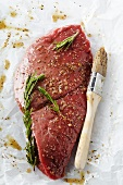 Raw Steak in a Rosemary Marinade on Butcher's Paper; Basting Brush