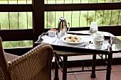 Holztablett mit Frühstück auf einem kleinen Tisch neben Rattanstuhl