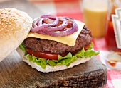 Cheeseburger on rustic chopping board