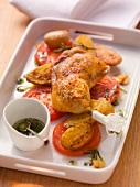 Fried chicken legs with roast potatoes and sliced tomatoes