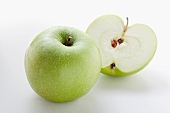 Whole apple and halved apple (variety: Granny Smith)