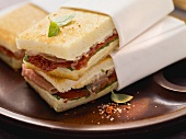 Toasted tramezzini with ham and dried tomatoes