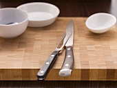 Chopping board with carving knife and fork and bowls