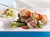 Marinated meat skewers on okra pods with tzatziki