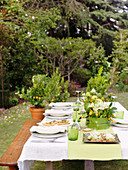 A table laid in a garden with table decoration and appetizers