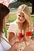 Zwei junge Frauen mit Getränk beim Picknick