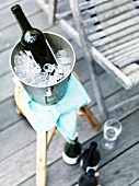 Bottle of red wine in an ice bucket on a stool on a veranda