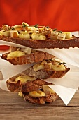 Stack of baguette slices with brie, pear & walnuts