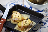 Potatoes topped with grilled cheese in a raclette pan
