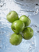Five Granny Smith apples dropping into water
