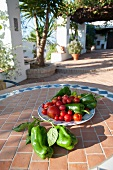 Peppers and tomatoes on a tiled garden table in a courtyard