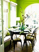 A table laid in a green painted living room