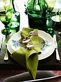A place setting on a table laid with green glasses, bottle and napkins