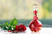 Rosenessig in der Flasche mit Rose