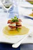Layered dish of scallops and prosciutto with pumpkin and coconut sauce