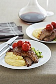 Veal escallops with lemon, oregano, mashed potato and balsamic tomatoes