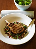 Pork chop on lentils with pancetta