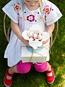 Mädchen hält einen Karton Marshmallows
