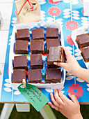A child's hand reaching for a slice of chocolate and raspberry cake at a school fete