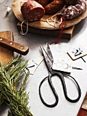 Various types of sausages, a pair of herb scissors and signs with numbers