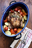 Chicken with pumpkin, potatoes and tomatoes in roasting dish