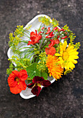 Brightly coloured, cottage-garden flowers in white dish
