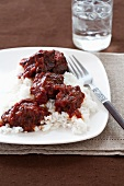 Barbecue Steak Tips on a Bed of Rice; Glass of Water