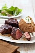 Sirloin Steak Tips with a Baked Potato; Piece of Steak on Fork