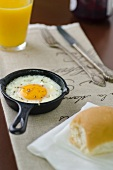 Fried egg in little frying pan with bread roll and orange juice
