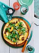 Pizza mit Schweinefleisch, Provolone, Pfirischspalten und Rucola