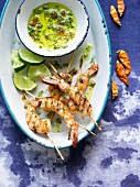 Platter of Grilled Skewered Shrimp with Herb Sauce and Limes