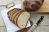 Rustic bread baked in a wood-fired oven, whole loaf and sliced