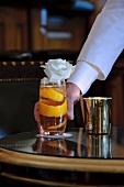 Cocktail mit Orangenschale und Blumendeko