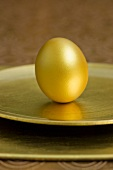 Gold Easter egg on a gold plate