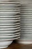 A close-up of two stacks of white plates