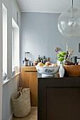 Schlicht aber edel gestaltete Küchenschrankelemente in Naturholz und Anthrazit zu Kugelglaslampe im Retrostil