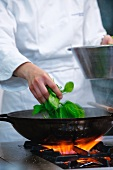 A chef adding spinach to a pan